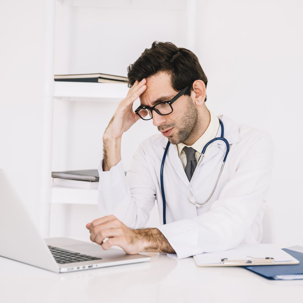 Physician looking tired with laptop